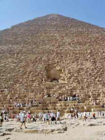 A line of tourists wait to enter the pyramid, while the true entrance stands above, unused.